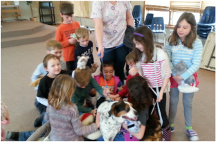 A group of young children stand with a canine visitor.