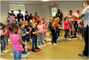 A room full of elementary school students stands to practice how to greet a strange dog.